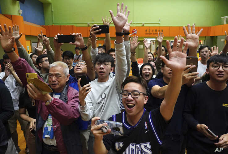 Supporters of pro-democracy candidate Angus Wong celebrate after he won in district council elections in Hong Kong