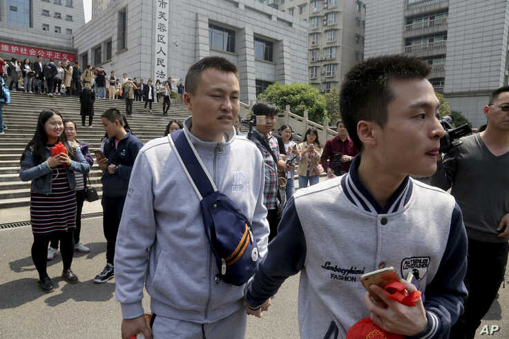 FILE - In this April 13, 2016, file photo, Sun Wenlin, right, and his partner Hu Mingliang leave the court after a judge ruled…