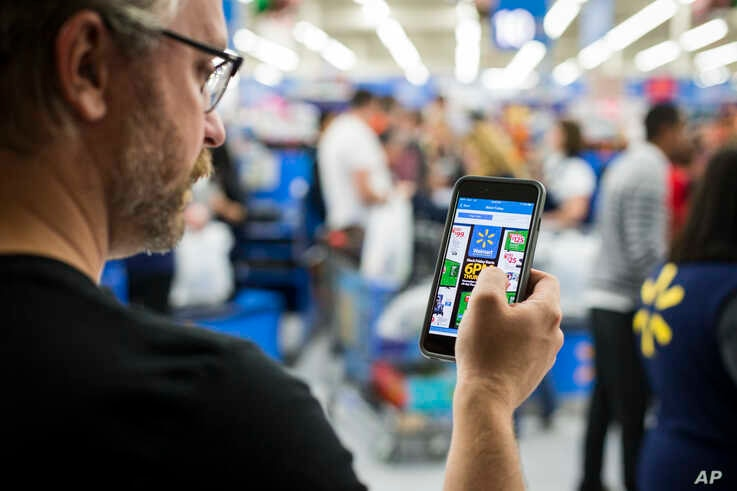 File --Customer uses his phone as a shopping tool during Black Friday at Walmart in Bentonville, Arkansas, Nov. 24, 2016.