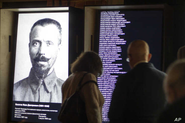 FILE - Visitors look at an exposition at the opening of the Gulag history museum in Moscow, Russia, Oct. 30, 2015.