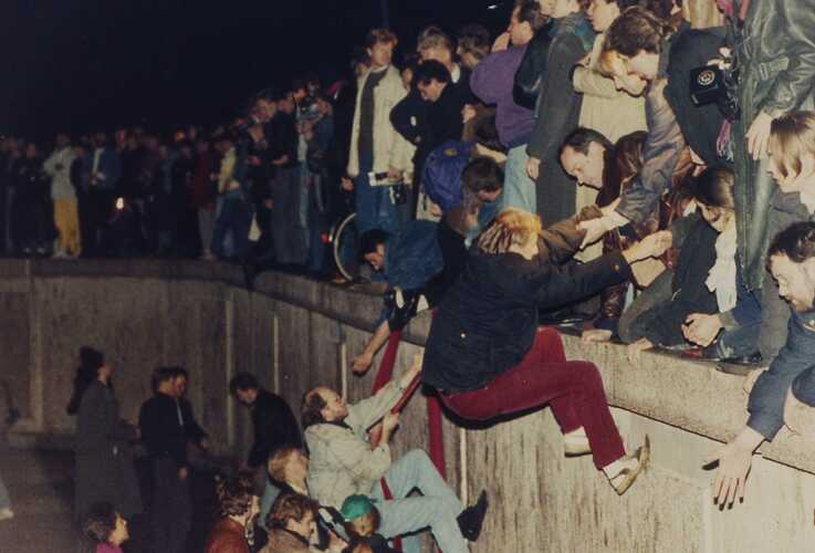 FILE - This Nov. 10, 1989 file photo shows East Berliners getting helping hands as they climb the Berlin Wall.