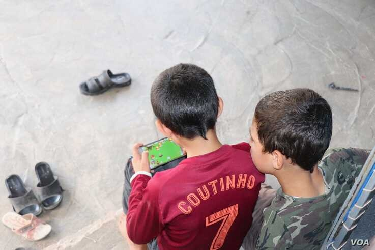Maher plays video games as his brother looks on, in Khanke, Kurdistan region, Iraq, Sept. 28, 2019. The boys were kidnapped nearly five years ago and sold to separate buyers. (Heather Murdock/VOA)