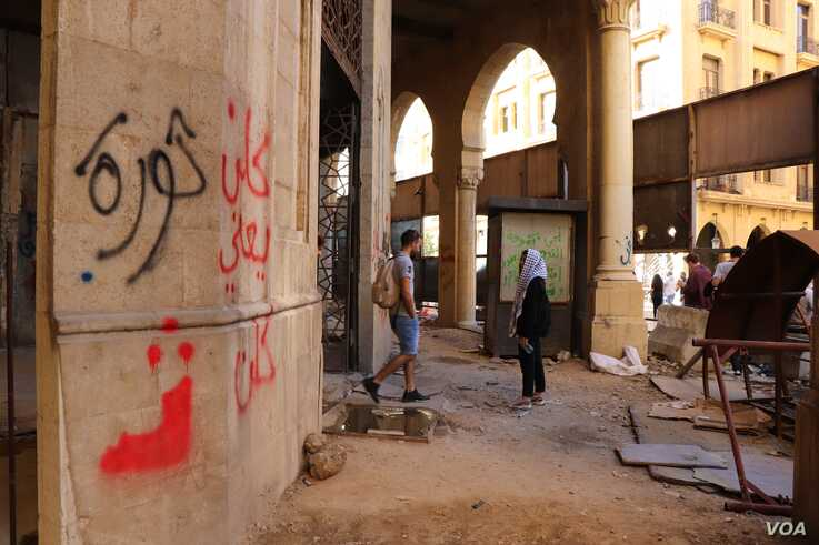 """Many of the boards closing up this abandoned building have been torn down and graffiti, including writing that says """"revolution"""" and """"all of them means all of them,"""" now covers the walls, in Beirut, Nov. 19, 2019. (Heather Murdock/VOA)"""