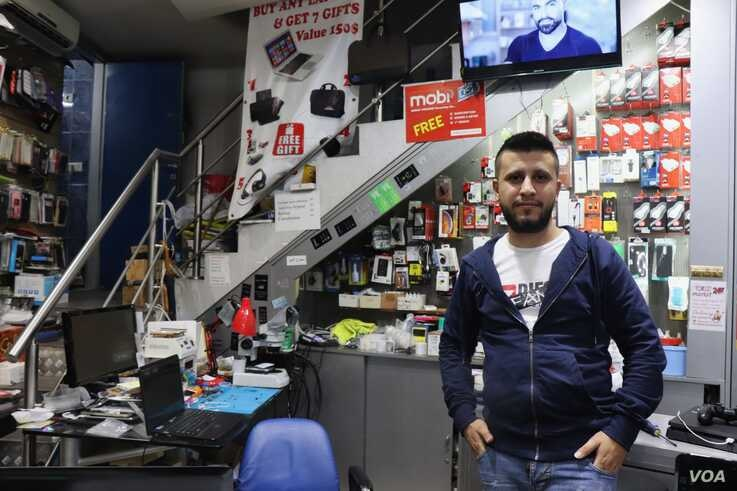 Malak, 27, lost 20 percent of his salary when the Lebanese dollar crisis began while his colleague lost his job entirely, in Beirut, Nov. 21, 2019. (Heather Murdock/VOA)