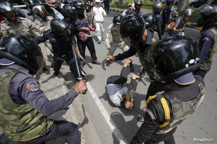 A man tries to protects himself as security forces beat him during the International Workers' Day rally at Freedom Park in…