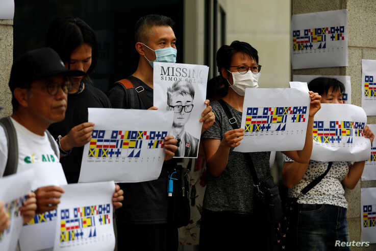 A demonstrator holds a poster of Simon Cheng, a staff member at the consulate who went missing on August 9 after visiting the…
