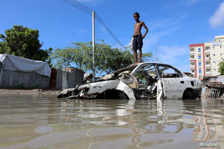 A Somali boy stands on a junk vehicle after heavy rain flooded their neighbourhood in Mogadishu, Somalia October 21, 2019.