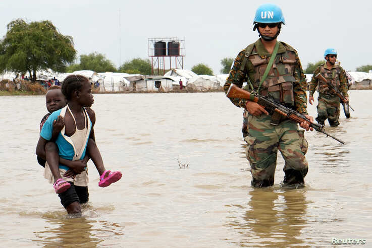 A girl holding a child walks past UN peacekeepers, after heavy rains and floods forced hundreds of thousands of people to leave their homes, in the town of Pibor, Boma state, South Sudan, Nov. 6, 2019.