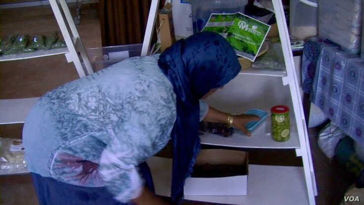 Samira Sghaier arranges a shelf with her moringa products. She's had a hard time finding buyers. (Lisa Bryant/VOA)