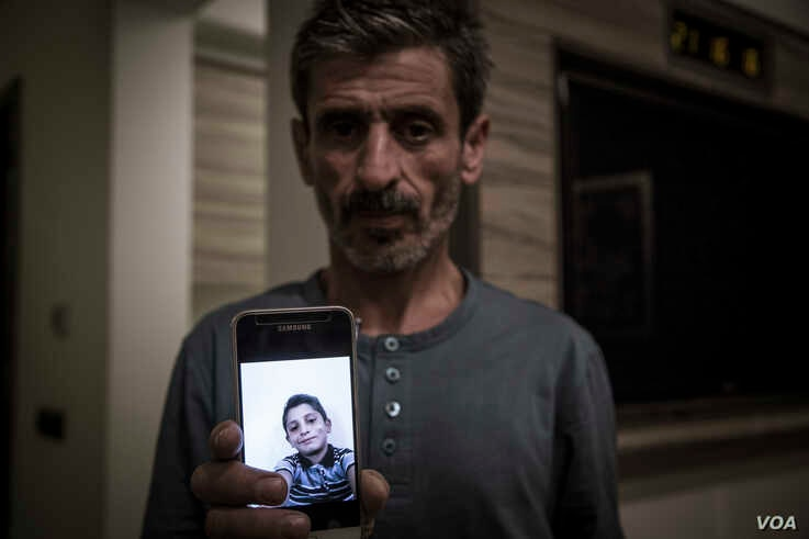 Syrian Kurd Yusf Hussein shows a photo of his son Muhammed, 13, who was killed by Turkish mortars in Turkey's incursion into northern Syria, in Sulaymaniyah, northern Iraq, Oct. 30, 2019. (Rebaz Majeed/VOA)
