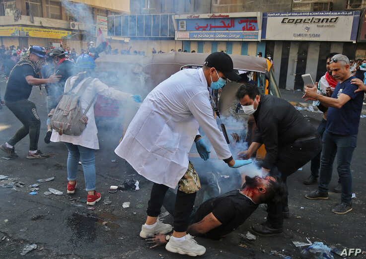 Iraqi volunteers help a protester who was struck by a tear gas canister fired by security forces at Baghdad's Khallani square during ongoing anti-government demonstrations.