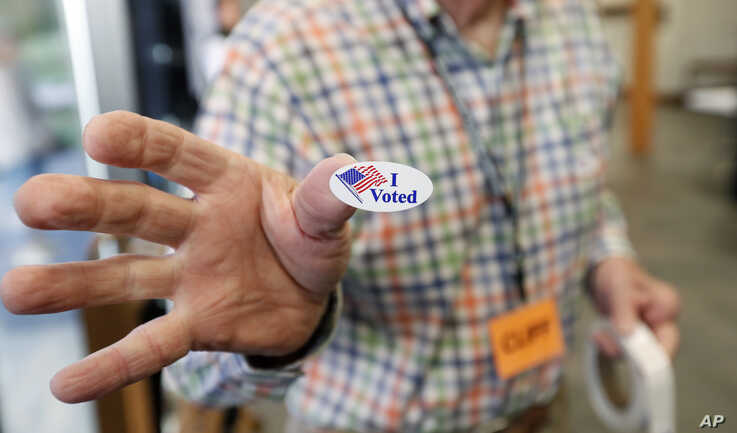"""Cliff Smith, a Ridgeland, Mississippi, poll worker, offers a voter an """"I Voted"""" sticker after they cast their ballot, Nov. 5, 2019."""
