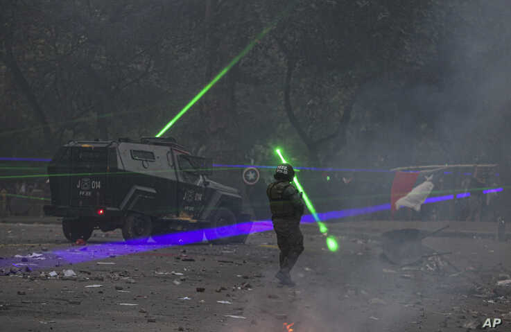 Anti-government demonstrators shine laser pointers at the police during a protest in Santiago, Chile, Nov. 12, 2019.
