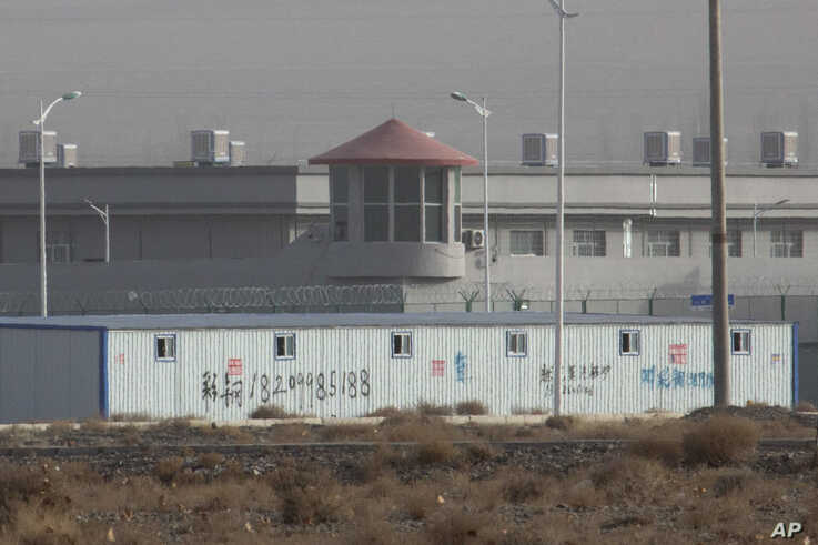 FILE.- A guard tower and barbed wire fences are seen around a facility in the Kunshan Industrial Park in Artux in western China's Xinjiang region, Dec. 3, 2018.