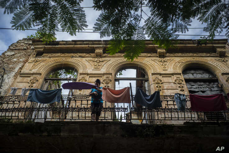 A woman pulls towels off the line after they dried on the balcony of an old home, missing part of its roof, in Havana, Cuba, Nov. 10, 2019.