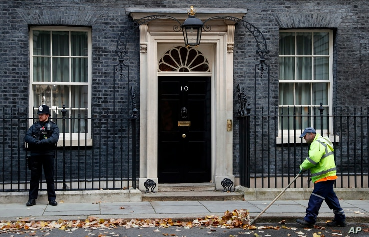 FILE - A street cleaner clears fall leaves from the front of 10 Downing Street, London, Britain, Nov. 6, 2019.