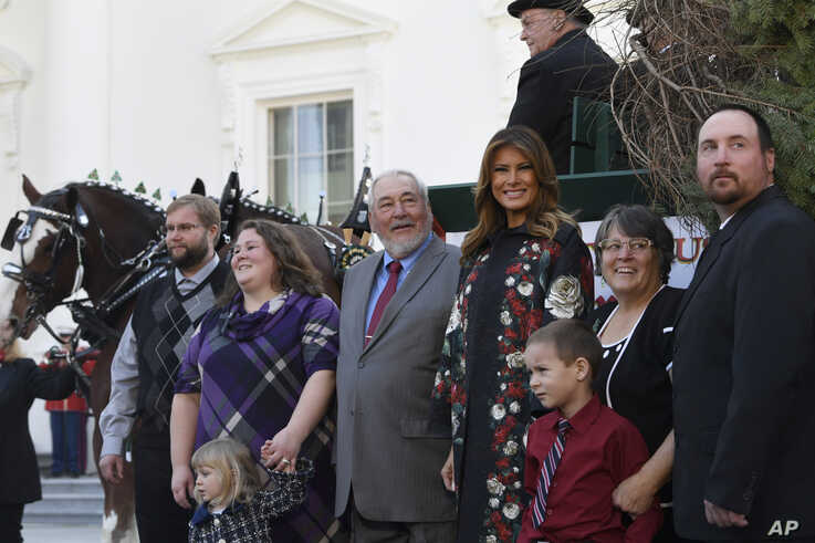 First lady Melania Trump poses with the 2019 White House Christmas tree as it is delivered to the White House in Washington, Nov. 25, 2019. The tree came from the Pennsylavia farm of Larry Snyder, third from left, pictured here with his family.