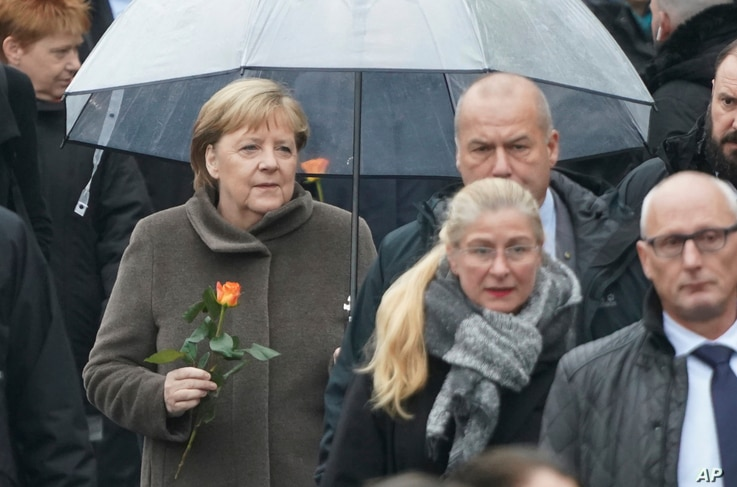 German Chancellor Angela Merkel arrives with a rose at a ceremony marking the 30th anniversary of the fall of the Berlin  Wall, in Berlin, Germany, Nov. 9, 2019.