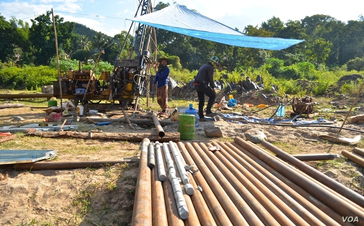 Workers operate a drill to test the bedrock for construction of the Luang Prabang dam near Houaygno village, Laos, Nov. 4, 2019.