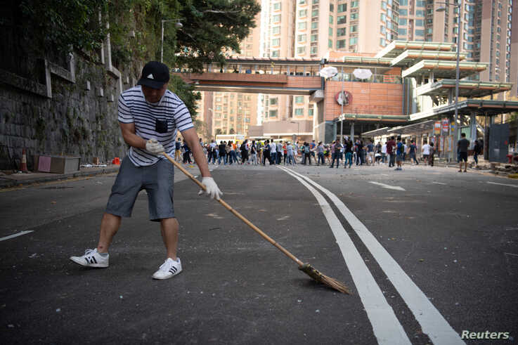 A man sweeps the street as people clear makeshift barricades erected by protesters, outside the University of Hong Kong, in Hong Kong, China, Nov. 16, 2019.