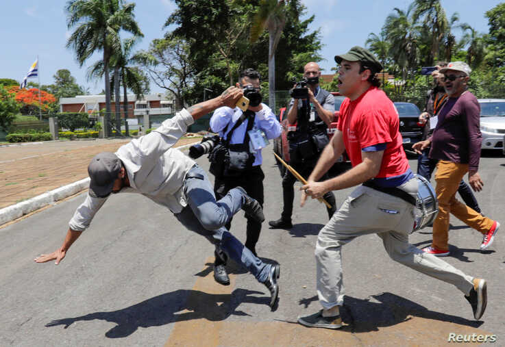 A supporter of Venezuela's President Nicolas Maduro fights with an opposition leader Juan Guaido's supporter outside Venezuelan embassy in Brasilia, Brazil, Nov. 13, 2019.