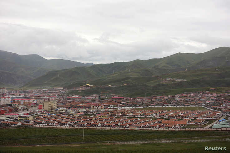 FILE - Houses for nomad families relocated from Madoi county are seen at the resettlement village of Heyuan inside a walled compound in Maqen county, Golog Tibetan Autonomous Prefecture, Qinghai province, China, Aug. 30, 2019.
