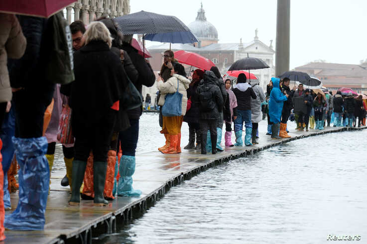 People walk on a catwalk in the flooded St. Mark's Square during a period of seasonal high water in Venice, Italy, Nov. 12, 2019.