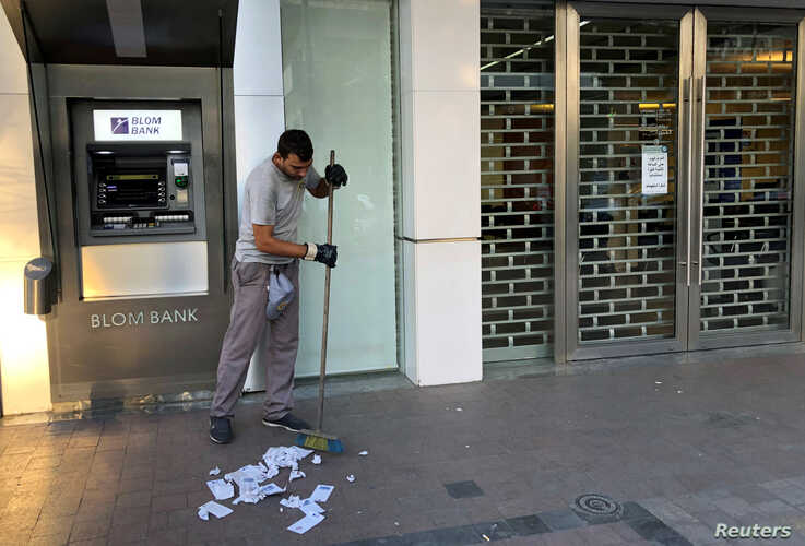 A worker cleans receipts from an ATM machine outside a closed Blom Bank branch in the southern city of Sidon, Lebanon, Nov. 12, 2019.