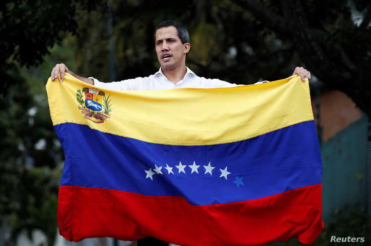 Venezuelan opposition leader Juan Guaido, who many nations have recognized as the country's rightful interim ruler, waves the Venezuelan flag at a gathering with supporters near Bolivia's embassy in Caracas, Venezuela, Nov. 16, 2019.