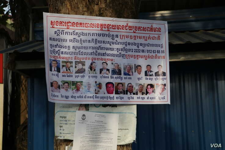 A banner displaying photos of the 18 senior CNRP leaders wanted for arrest is plastered on a tree in Poipet, Banteay Meanchey pr