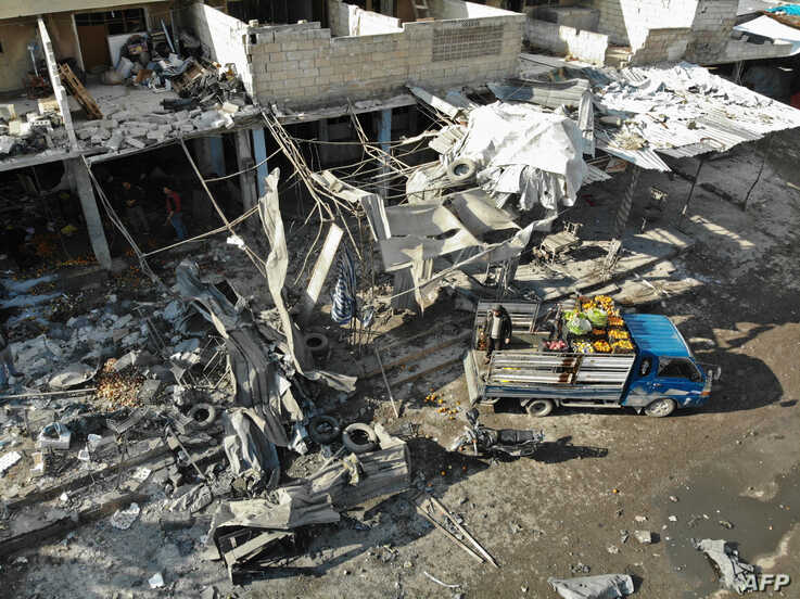 An aerial view shows the destruction following a regime air strike on December 2, 2019 in a market in the town of Maaret al…