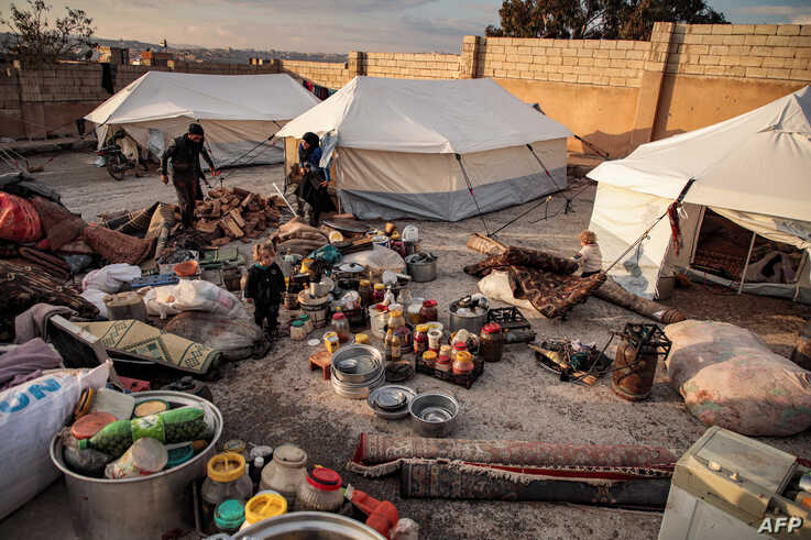 This picture taken on December 27, 2019 shows a view of supplies outside tents of displaced Syrians, who fled from government…