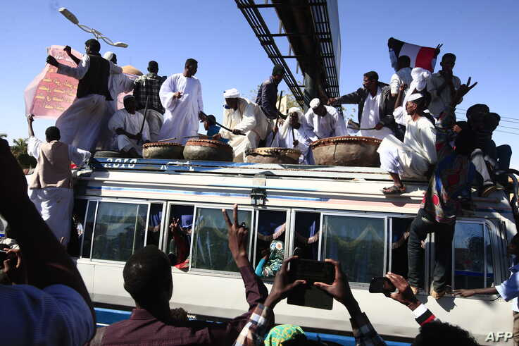 Sudanese protesters sit on the roof of a bus as they rally in front of a court in Omdurman near the capital Khartoum during the…