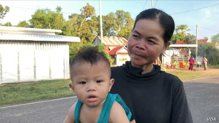 Sim Lat, 40, carries her nephew Ham Ya Oudom on a walk while waiting for his mom to come back from work, at Svay Ta Yean commune, Svay Rieng province, Cambodia, Oct. 11, 2019. (Khan Sokummono/VOA Khmer)