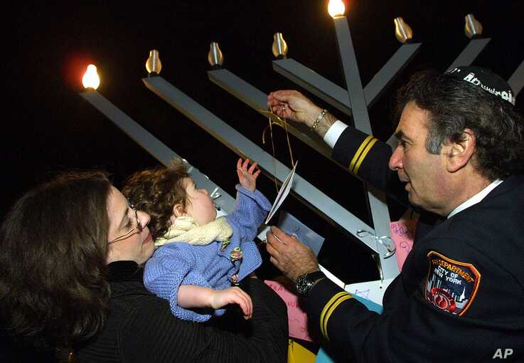 FILE - Rabbi Potas Nik, right, helps Hayley Lehrfeld of Brooklyn Heights, NY, and her daughter Laura, place a card after lighting a menorah on the first day of Hanukkah near the remains of the World Trade Center complex in New York.