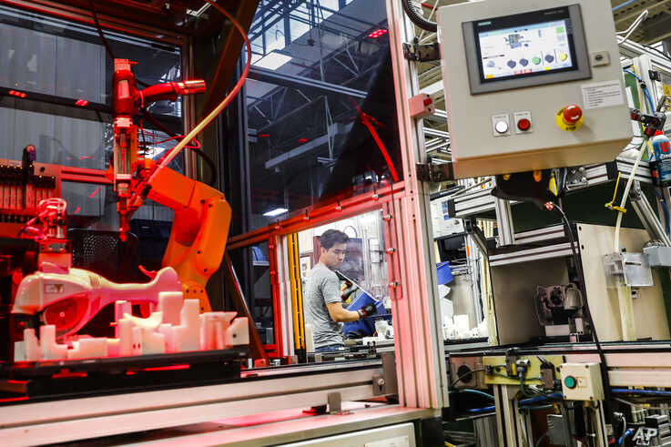 In this May 25, 2017, file photo, an assembly line laborer works alongside a collaborative robot at the Stihl Inc. production plant in Virginia Beach, Virginia.