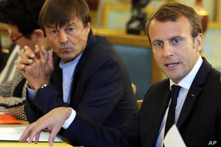 FILE - In this Sept.5 2017 file photo, French President Emmanuel Macron, right, and Environment Minister Nicolas Hulot meet…