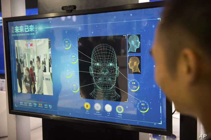 A man watches as a visitor tries out a facial recognition display at a booth for Chinese tech firm Ping'an Technology at the Global Mobile Internet Conference (GMIC) in Beijing, April 26, 2018.