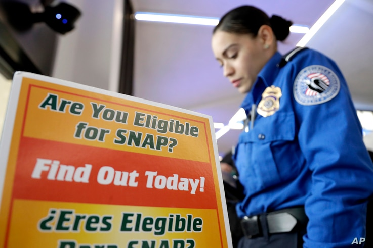 A Transportation Security Administration employee stands at a booth to learn about a food stamp program at a food drive at…