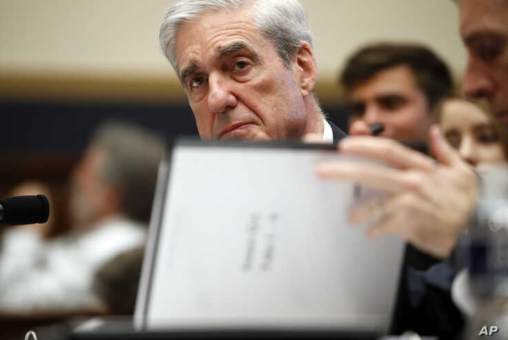 Former special counsel Robert Mueller, checks pages in the report as he testifies before the House Judiciary Committee