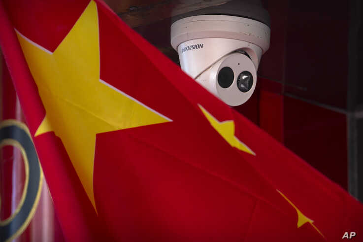 A Chinese flag hangs near a Hikvision security camera outside of a shop in Beijing, Oct. 8, 2019.