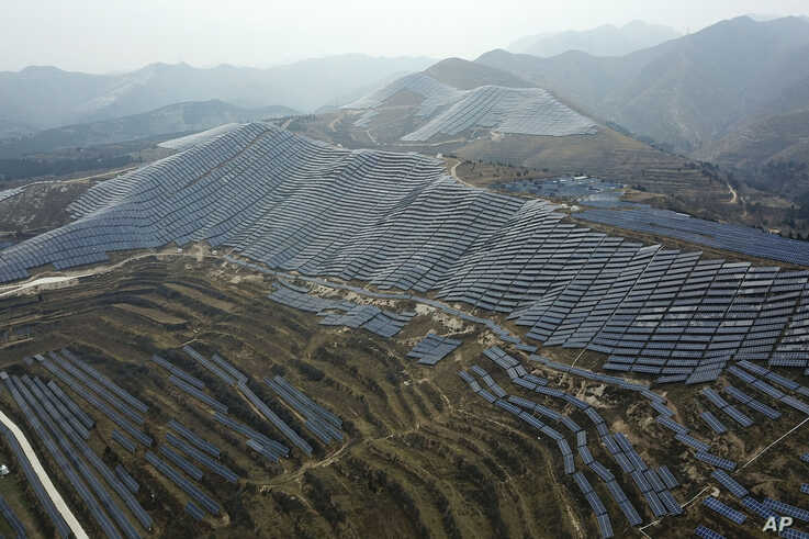 In this Nov. 27, 2019, photo, a solar panel installation is seen in Ruicheng County in central China's Shanxi Province. As…