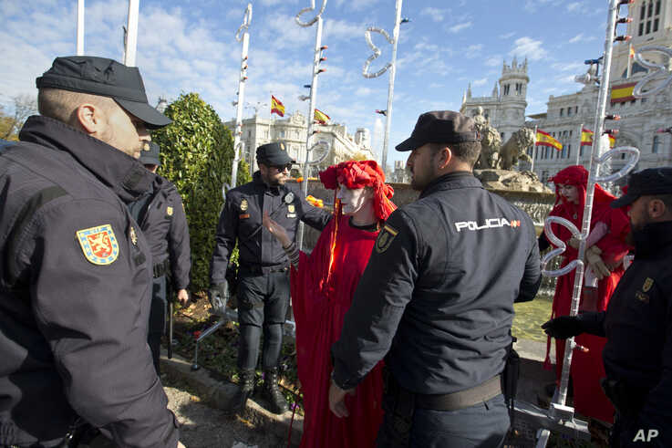 Police remove activists at the Cibeles fountain during a protest performance in Madrid, Spain, Tuesday, Dec. 3, 2019. Some 20…