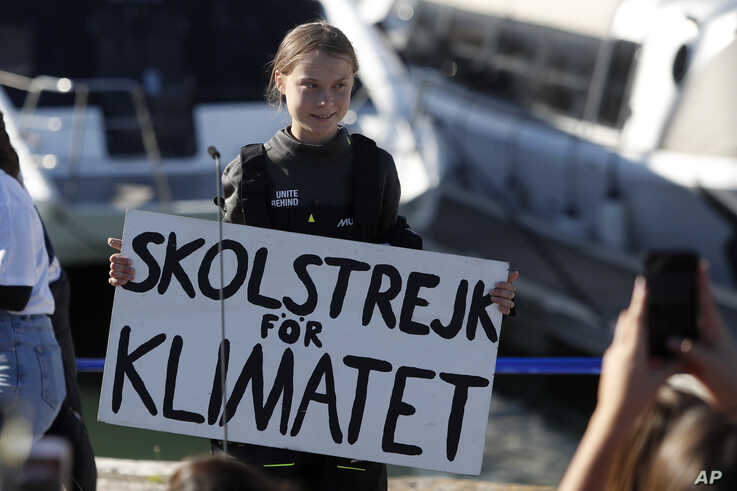 Climate activist Greta Thunberg holds a sign reading 'School strike for the climate' after arriving in Lisbon, aboard the…