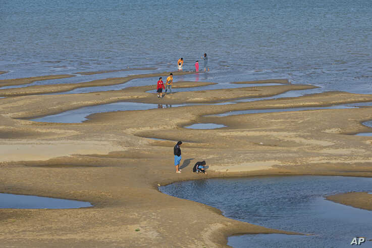 In this Wednesday, Dec. 4, 2019, photo, sightseers plays on a sandbar in the Mekong River in Nakhon Phanom province,…