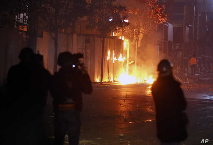 Hezbollah and Amal supporters set fire to trees in Beirut, Lebanon, Tuesday, Dec. 17, 2019. Supporters of Lebanon's two main…
