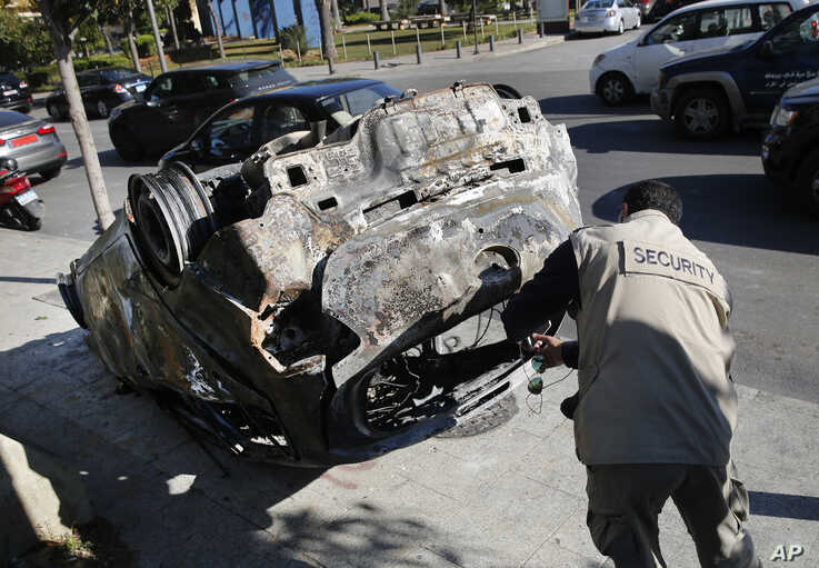 A private security worker takes pictures of a burned car that was set on fire early Tuesday by supporters of the Shiite…