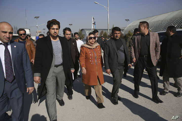 Hawa Alam Nuristani, chief of Election Commission of Afghanistan, center, leaves after a press conference at the Independent Election Commission office in Kabul, Afghanistan, Dec. 22, 2019.