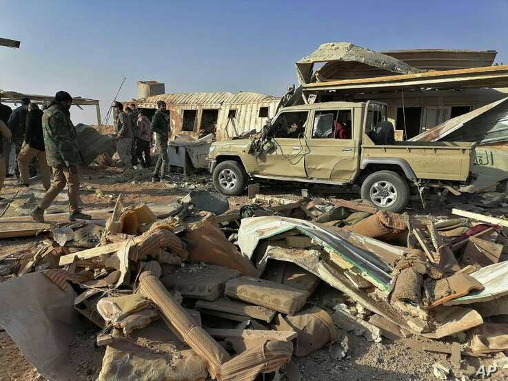 Fighters from the Kataeb Hezbollah, or Hezbollah Brigades militia, inspect the destruction at their headquarters in the…
