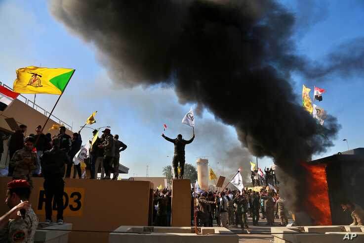 Protesters burn property in front of the U.S. embassy compound, in Baghdad, Iraq, Dec. 31, 2019.